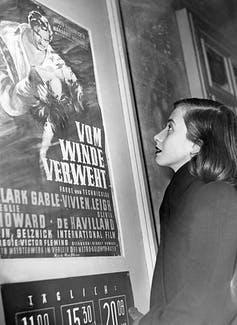 A woman looks at a movie poster of 'Gone with the Wind.'
