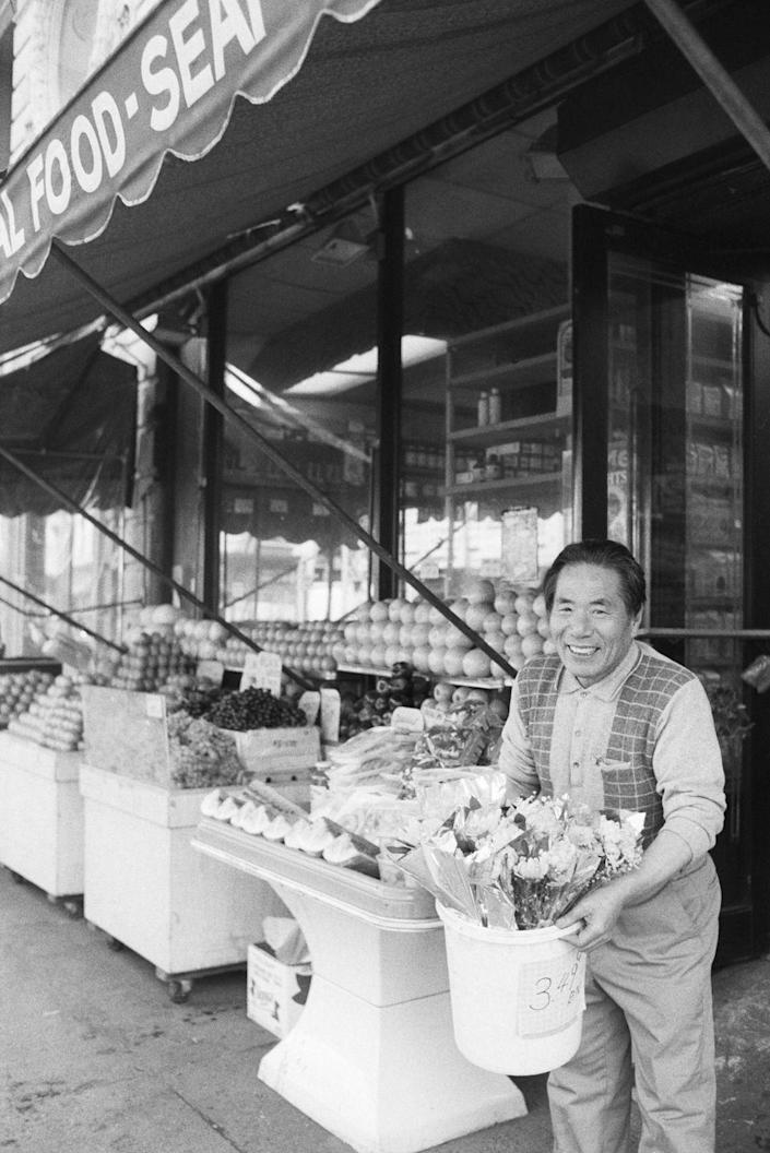 """<p>A grocer puts fresh flowers outside of his small corner market. According to the Labor Market Information Service, there are over <a href=""""http://www.nyc.gov/html/sbs/wib/downloads/pdf/grocery_stores.pdf"""" rel=""""nofollow noopener"""" target=""""_blank"""" data-ylk=""""slk:5,000 grocery stores in New York City"""" class=""""link rapid-noclick-resp"""">5,000 grocery stores in New York City</a> alone.</p>"""