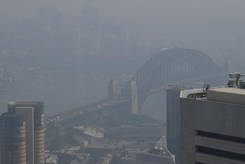 The Sydney Harbour Bridge can be seen through a thick blanket of smoke hanging over Sydney's central business district as seen from The Sydney Tower Eye.