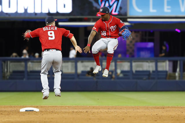 Washington Nationals' Brian Dozier (9) and Victor Robles (16) celebrate after they defeated the Miami Marlins in 10 innings of a baseball game Saturday, Sept. 21, 2019, in Miami. (AP Photo/Wilfredo Lee)