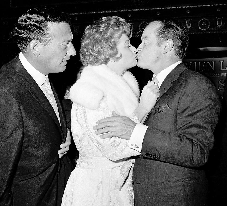<p>Lucille Ball and Bob Hope share a smooch, while Ball's soon-to-be-husband, Gary Morton, looks on at the premiere of <em>Bachelor in Paradise</em>, 1961.</p>
