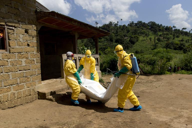Guinean Red Cross workers wearing protective suits carry the corpse of a victim of Ebola in Macenta on November 21, 2014