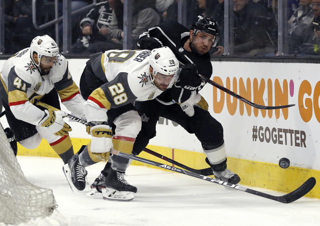 Los Angeles Kings defenseman Alec Martinez, right, competes for the puck with Vegas Golden Knights left wing William Carrier, center, and left wing Pierre-Edouard Bellemare, left, of France, during the third period of Game 4 of an NHL hockey first-round playoff series in Los Angeles, Tuesday, April 17, 2018. Vegas won 1-0, becoming the first expansion team in NHL history to sweep its first playoff series. (AP Photo/Alex Gallardo)