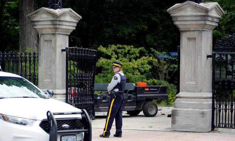 A police officer stands near a damaged gate at Rideau Hall, where Justin Trudeau lives.