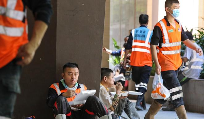 Workers having their lunch on a roadside in Wan Chai on Thursday. Photo: K. Y. Cheng