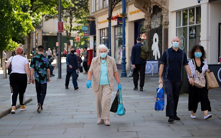 People wear face masks in the town centre of Newport, Wales. - Getty Images Europe