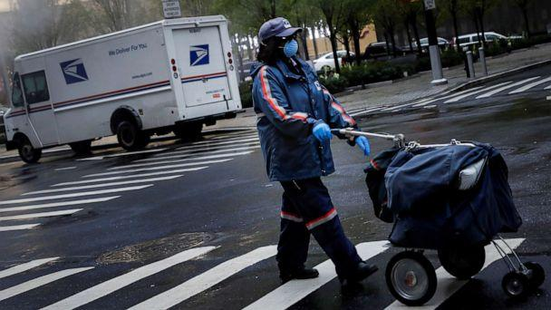 PHOTO: A United States Postal Service (USPS) worker works in the rain in Manhattan during the outbreak of the coronavirus disease (COVID-19) in New York, April 13, 2020. (Andrew Kelly/Reuters)