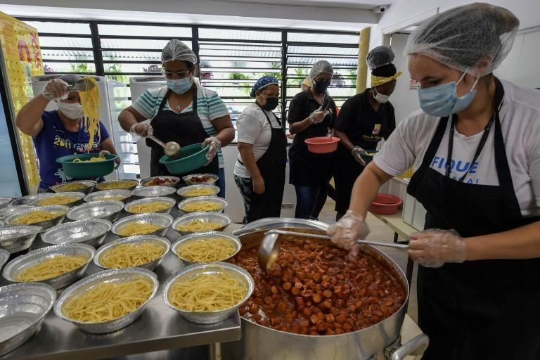 Workers prepare meals at a soup kitchen in Paraisopolis favela, where traditional loans are a nearly impossible dream for households and businesses
