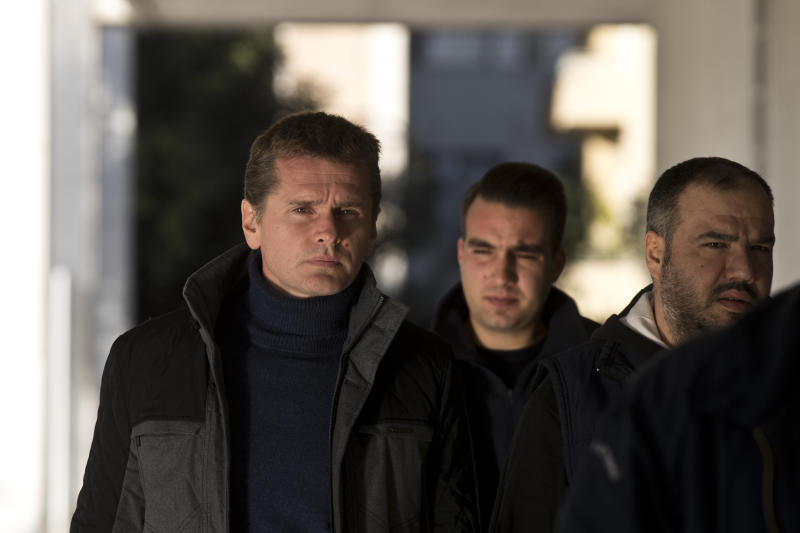 FILE - In this Wednesday, Dec. 13, 2017 file photo, Russian cybercrime suspect Alexander Vinnik, left, arrives at Greece's supreme court in Athens. Greece's justice minister has signed an order on Friday, Dec. 20, 2019, for bitcoin fraud suspect Alexander Vinnik to be extradited to France - concluding an international legal battle surrounding the Russian former cryptocurrency trading platform operator. (AP Photo/Petros Giannakouris, file)