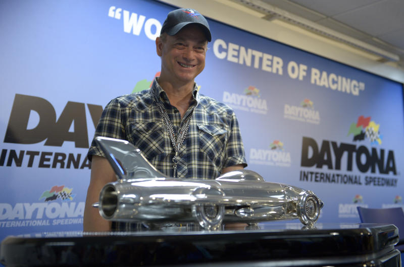 Actor Gary Sinise poses with the winner's trophy for the NASCAR Daytona 500 Sprint Cup series auto race at Daytona International Speedway during a news conference in Daytona Beach, Fla., Sunday, Feb. 23, 2014. (AP Photo/Phelan M. Ebenhack)