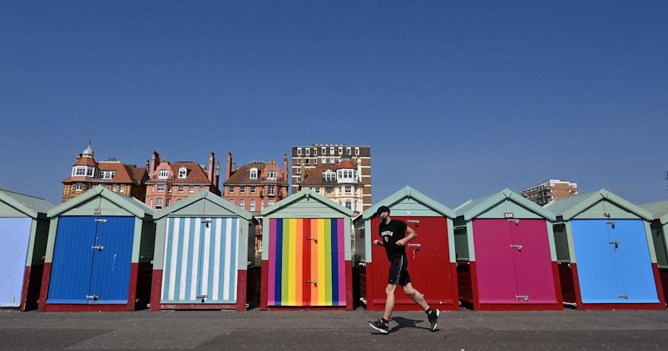 A man runs past beach huts along the seafront in Brighton, on the south coast of England on April 10 2020 - GLYN KIRK/AFP via Getty Images