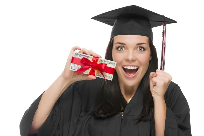 A woman in a black cap and gown holding cash tied up with a red bow