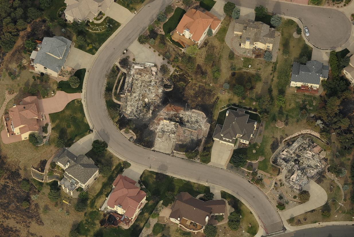 In this aerial photo, homes untouched by the Waldo Canyon fire stand next to the charred lots where neighboring homes were burned to the ground in the Mountain Shadows subdivision area of Colorado Springs, Colo., Thursday, June 28, 2012. Colorado Springs officials said Thursday that hundreds of homes have been destroyed by the raging wildfire. (AP Photo/Denver Post, RJ Sangosti)
