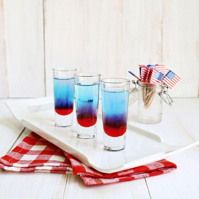 """<p>This shot is basically your favorite patriotic popsicle from your childhood, but boozy. It's made with grenadine, Mike's Hard Lemonade, and blue curaçao.</p><p><strong>Get the recipe at <a rel=""""nofollow"""" href=""""http://abeautifulmess.com/2014/07/bomb-pop-shots.html"""">A Beautiful Mess</a>.</strong></p>"""