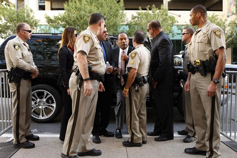 FILE - In this Sept. 9, 2008, file photo, O.J. Simpson, center, arrives at the Clark County Regional Justice Center on the second day of jury selection for his trial in Las Vegas. Simpson is appearing in court on charges which include burglary, robbery and assault following an attempted robbery at the Palace Station Hotel & Casino in Las Vegas on September, 2007. The return of O.J. Simpson to a Las Vegas courtroom next Monday, May, 13, will remind Americans of a tragedy that became a national obsession and in the process changed the country's attitude toward the justice system, the media and celebrity. The return of O.J. Simpson to a Las Vegas courtroom next Monday, May, 13, will remind Americans of a tragedy that became a national obsession and in the process changed the country's attitude toward the justice system, the media and celebrity. (AP Photo/Las Vegas Review-Journal, John Locher, Pool, File)