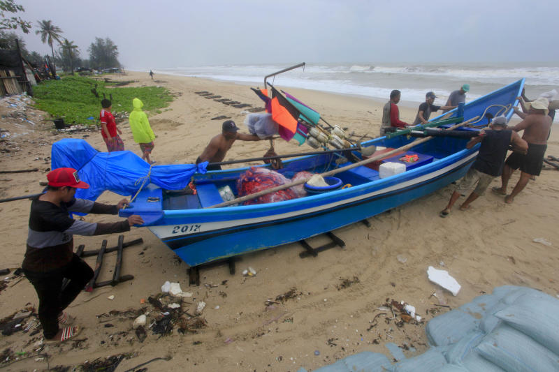 Thai men push a fishing boat off the ocean to a safer location in Songkhla, Thailand in preparation for storm weather conditions on Thursday, Jan. 3, 2019. Thai weather authorities are warning that a tropical storm will bring heavy rains and high seas to southern Thailand and its famed beach resorts. (AP Photo/Sumeth Panpetch)