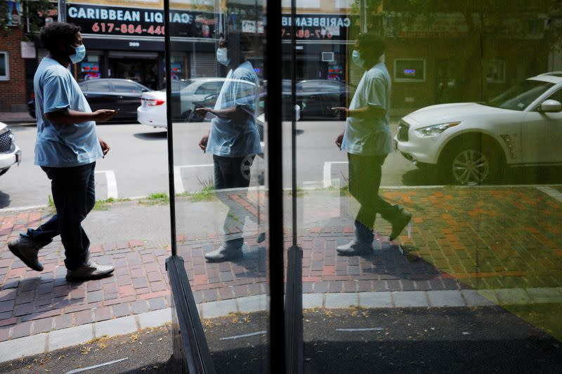 A pedestrian is reflected in the window of an empty storefront in Chelsea