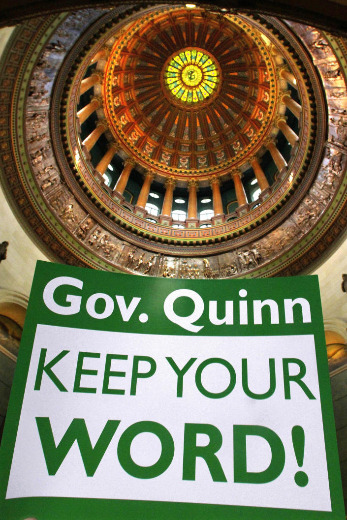 In this photo taken Feb. 2012, a sign held up by a member of the American Federation of State, County and Municipal Employees union is seen during a rally in front of the governor's office at the Illinois State Capitol in Springfield, Ill. The Pew Center on the States releases a 50-state report that finds the gap between the promises states have made for public employeesÕ retirement benefits and the money they have set aside has grown. (AP Photo/Seth Perlman)