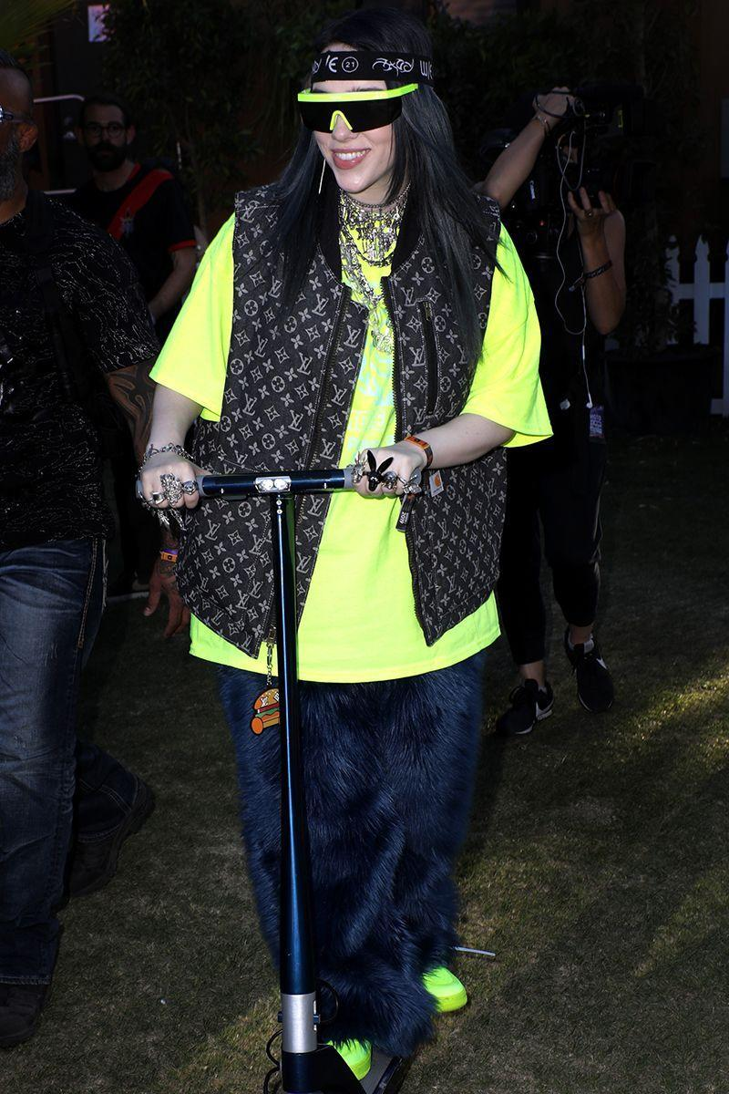 <p>Billies does Coachella style her way with neon visor glasses, a logo vest, and baggy tee. </p>