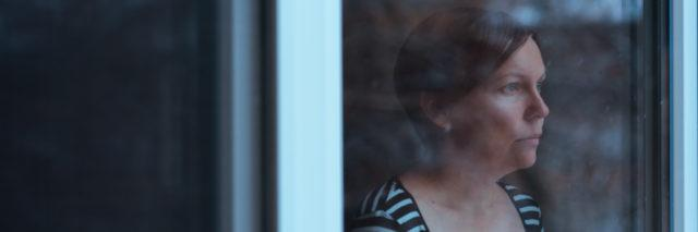 woman with short red hair in a striped shirt looking out the window solemnly
