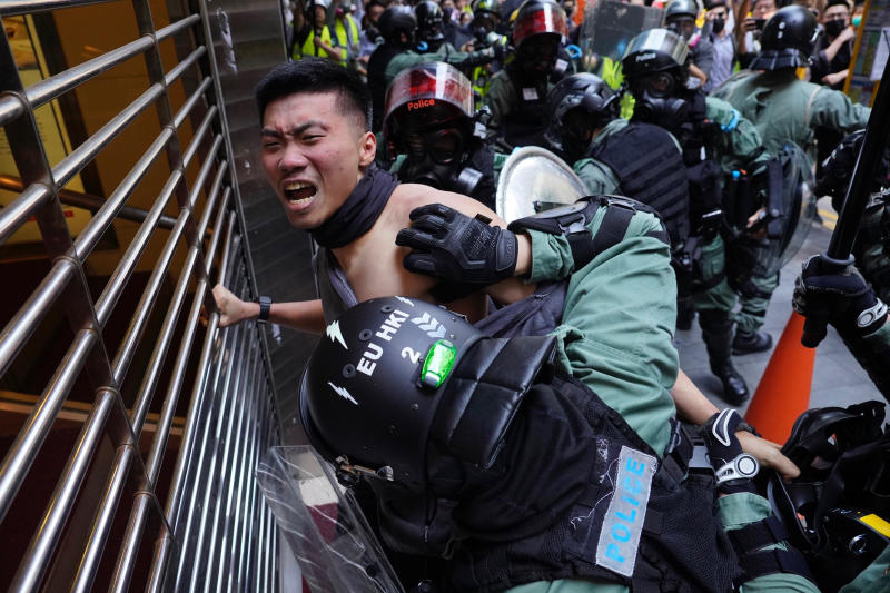 A protester is detained in Central district of Hong Kong on Monday, Nov. 11, 2019. A Hong Kong protester was shot by police Monday in a dramatic scene caught on video as demonstrators blocked train lines and roads during the morning commute. (AP Photo/Vincent Yu)