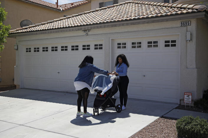 In this April 17, 2020, photo, Kimberly Ireland, left, helps her daughter Kyla Ireland, right, cover Kyla's three-week-old baby before going on a walk in Las Vegas. A walk around the neighborhood is one of the rare times they leave the house during the coronavirus outbreak. Kimberly Ireland was laid off from her job as a bell desk dispatcher at the Mirage casino-resort, where she worked for a decade. (AP Photo/John Locher)