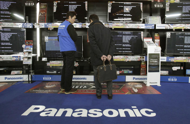 In this Thursday, Jan. 31, 2013 photo, a shopper speaks with a salesclerk in front of Panasonic flat-panel TVs at an electronics store in Tokyo. Japanese electronics maker Panasonic Corp. returned to the black last quarter as cost cuts and a weaker yen offset sliding sales. Panasonic is among the Japanese electronics makers battered by price plunges in gadgets and hot competition from more successful rivals such as U.S. manufacturer Apple Inc. and Samsung Electronics Co. of South Korea. Osaka-based Panasonic reported a 61.4 billion yen ($667 million) profit for the October-December period Friday, Feb. 1. (AP Photo/Shizuo Kambayashi)