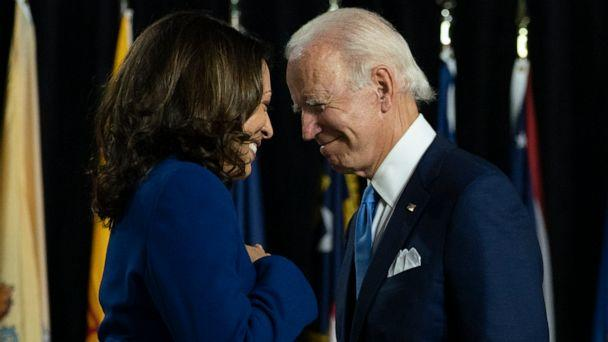 PHOTO: Former Vice President Joe Biden and his running mate Sen. Kamala Harris, D-Calif., pass each other as Harris moves to the podium to speak during a campaign event at Alexis Dupont High School in Wilmington, Del., Wednesday, Aug. 12, 2020. (Carolyn Kaster/AP)