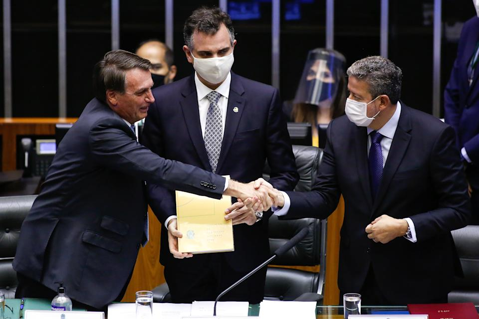 Brazilian President Jair Bolsonaro (L) shakes hands with the new president of the Chamber of Deputies, Arthur Lira (R), in front of the new president of the Federal Senate, Rodrigo Pacheco (C), during a session of the National Congress, in Brasilia, on February 3, 2021. - The Brazilian Congress on Monday elected two allies of President Jair Bolsonaro to head the Senate and the lower house, an important victory for the far-right leader in his quest to reinvigorate his reelection efforts for 2022. (Photo by Sergio Lima / AFP) (Photo by SERGIO LIMA/AFP via Getty Images)