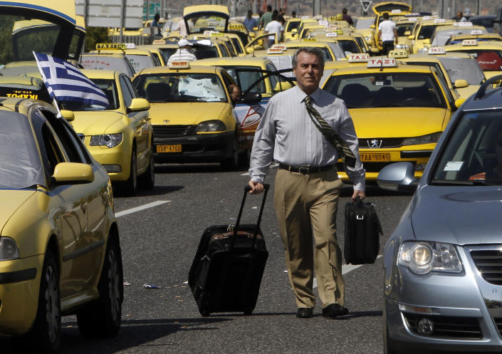 A commuter walks next to immobilized taxis during a protest near the Athens International airport, July 18, 2011. Greek taxi drivers blocked roads to Athens' airport and main harbour on Monday, holding up thousands of tourists at the start of a two-day protest against plans to liberalise their trade. (REUTERS/John Kolesidis)