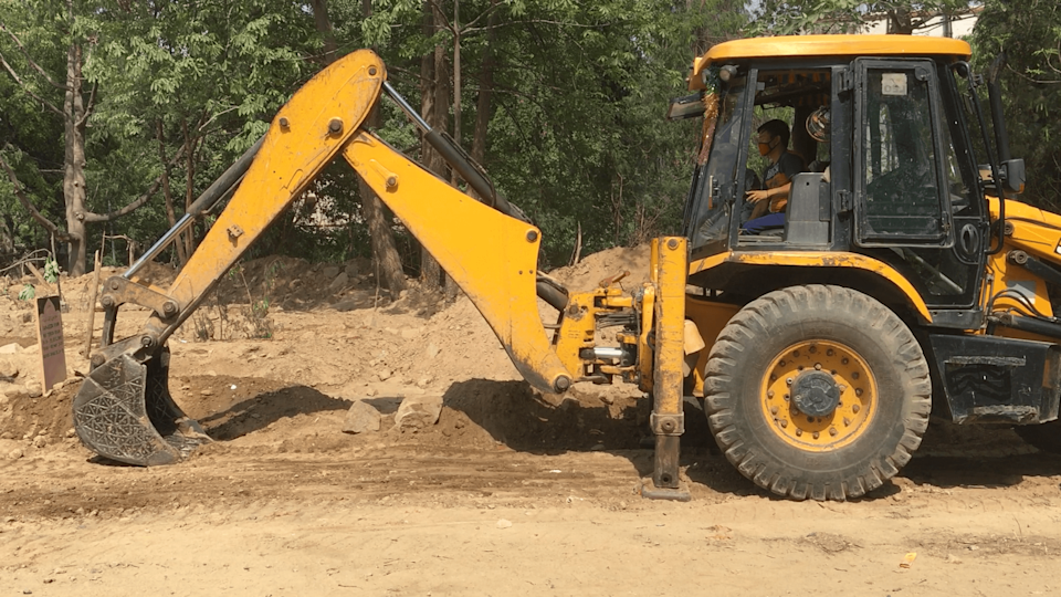 """Shamin said that generally the graves are dug manually by one person who takes about three hours to finish the digging. """"With the increase in numbers we had to get a JCB to do the digging, otherwise we were getting very delayed,"""" he said."""