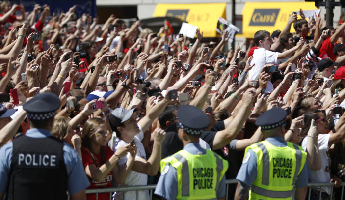 Chicago Blackhawks' fans takes pictures as Jonathan Toews and the Stanley Cup pass by during a victory parade down Washington Street Friday, June 28, 2013 in Chicago. The Blackhawks celebrate the team's second championship in four years. (AP Photo/Scott Eisen)
