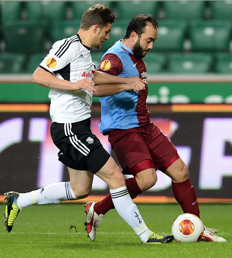 Legia Warsaw's Polish defender Bartosz Bereszynski (L) vies for the ball with Trabzonspor's midfielder Olcan Adin during a match on Novemver 7, 2013 in Warsaw