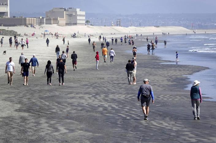"""People walk along the beach in Coronado, which is among the few remaining beaches open in San Diego County on March 29, 2020. <span class=""""copyright"""">(K.C. Alfred/The San Diego Union-Tribune)</span>"""