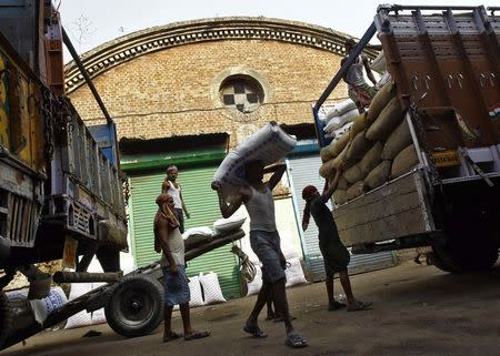 Labourers unload grocery items from supply trucks at a wholesale market in Kolkata