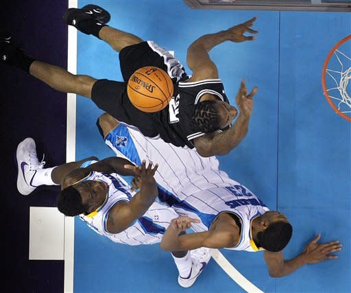 San Antonio Spurs small forward Kawhi Leonard drives to the basket against a falling New Orleans Hornets power forward Anthony Davis (23) in the first half of an NBA basketball game in New Orleans, Wednesday, Oct. 31, 2012. Bottom left is small forward Al-Farouq Aminu. (AP Photo/Gerald Herbert)