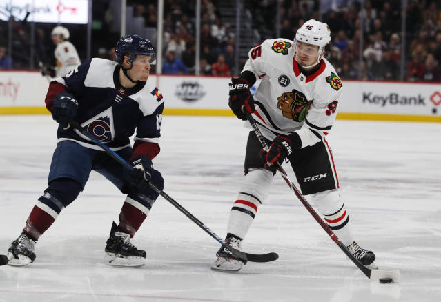 Chicago Blackhawks right wing Dylan Sikura, right, fires the puck at the net past Colorado Avalanche center Sheldon Dries in the second period of an NHL hockey game Saturday, Dec. 29, 2018, in Denver. (AP Photo/David Zalubowski)