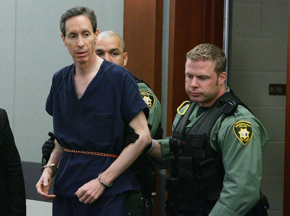 Warren Jeffs wearing a blue prison jumpsuit and handcuffs (L) is led by two Las Vegas Metropolitan Police Department SWAT officers into Las Vegas Justice Court for his extradition hearing at the Regional Justice Center August 31, 2006 in Las Vegas, Nevada.