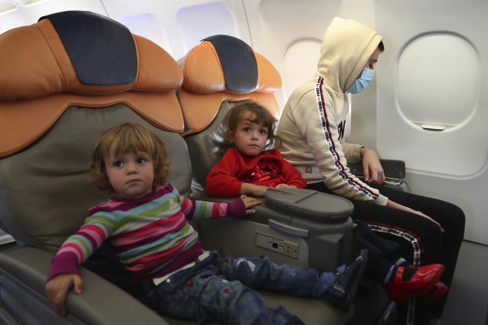 """Albanian children sit inside a plane before departing, during an operation to take them back home to Albania from al-Hol, northern Syria, in Beirut, Lebanon, Tuesday, Oct. 27, 2020. The repatriation of four children and a woman related to Albanian nationals who joined Islamic extremist groups in Syria """"is a great step"""" to be followed by more repatriations, Albania's prime minister said Tuesday in Beirut. (AP Photo/Bilal Hussein)"""