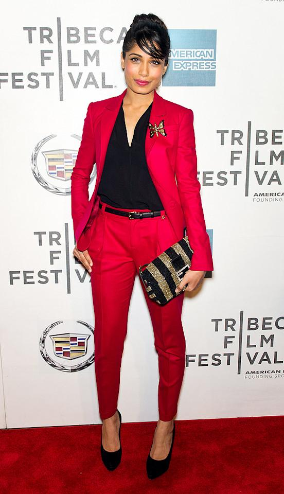 "Freida Pinto also opted for a masculine-looking ensemble this week. The ""Slumdog Millionaire"" alum attended the Tribeca Film Fest premiere of ""Trishna"" while wearing a gorgeous, raspberry-hued Gucci suit. The Indian beauty's brilliant accessories included a striped Fendi purse, butterfly brooch, black belt, and matching Gucci pumps. (4/27/2012)"