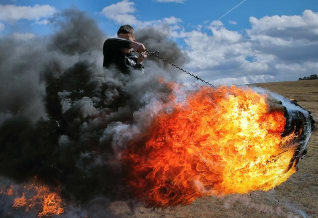 In this photo taken on Sunday, March 10, 2019, a young man spins a burning tire on a metal chain during a ritual marking the upcoming Clean Monday, the beginning of the Great Lent, 40 days ahead of Orthodox Easter, on the hills surrounding the village of Poplaca, in central Romania's Transylvania region. Romanian villagers burn piles of used tires then spin them in the Transylvanian hills in a ritual they believe will ward off evil spirits as they begin a period of 40 days of abstention, when Orthodox Christians cut out meat, fish, eggs, and dairy. (AP Photo/Vadim Ghirda)