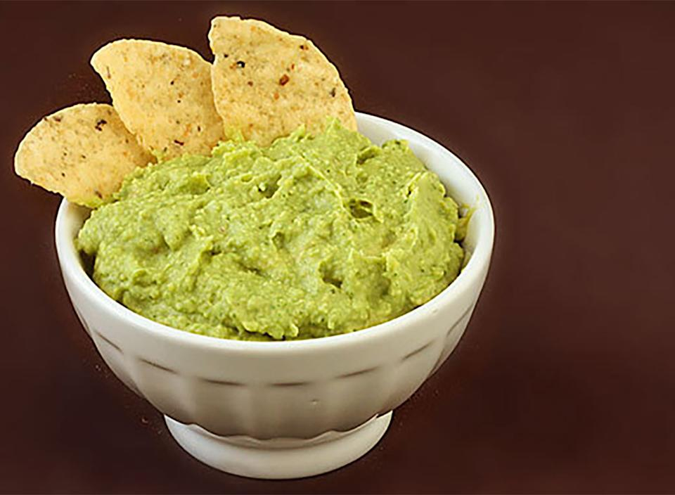 guacamole hummus in bowl with tortilla chip