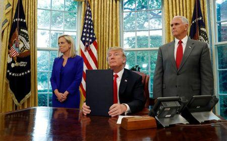U.S. President Donald Trump sits in front of the news media after signing an executive order on immigration policy with DHS Secretary Kirstjen Nielsen and Vice President Mike Pence at his sides in the Oval Office at the White House in Washington, U.S., June 20, 2018. REUTERS/Leah Millis