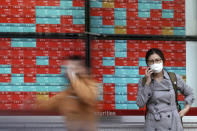 A woman talks on a mobile phone near an electronic stock board showing Japan's share prices at a securities firm in Tokyo Monday, Oct. 26, 2020. Asian shares were little changed in muted trading Monday amid widespread uncertainty over what the U.S. presidential election will portend for markets and economic policy.(AP Photo/Eugene Hoshiko)