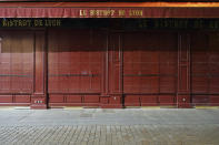 A closed restaurant is pictured after the start of the curfew in the empty center of Lyon, central France, Saturday, Oct. 17, 2020. France is deploying 12,000 police officers to enforce a new curfew that came into effect Friday night for the next month to slow the virus spread, and will spend another 1 billion euros to help businesses hit by the new restrictions. (AP Photo/Laurent Cipriani)