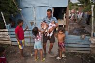 """In this April 8, 2013 photo, Eduardo Gonzalez, 30, holds his babies outside his aluminum shack in a squatter's settlement near Tacarigua, Venezuela. Outside Venezuela's capital, power outages, food shortages and unfinished projects abound; important factors heading into Sunday's election to replace Venezuela's late President Hugo Chavez, who died last month after a long battle with cancer. An estimated 2 million of Venezuela's country's nearly 30 million people lack permanent homes, and one of Chavez's anti-poverty """"missions"""" builds them. But it's been slow going. The government says it has built 370,500 homes and apartments over the past two years, and more than 3 million people applied for them. (AP Photo/Ramon Espinosa)"""