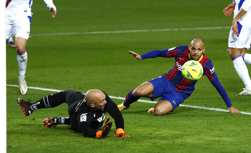 Barcelona's Martin Braithwaite, right, fails to score against Eibar's goalkeeper Marko Dmitrovic during the Spanish La Liga soccer match between Barcelona and Eibar at the Camp Nou stadium in Barcelona in Barcelona, Spain, Tuesday, Dec. 29, 2020. (AP Photo/Joan Monfort)