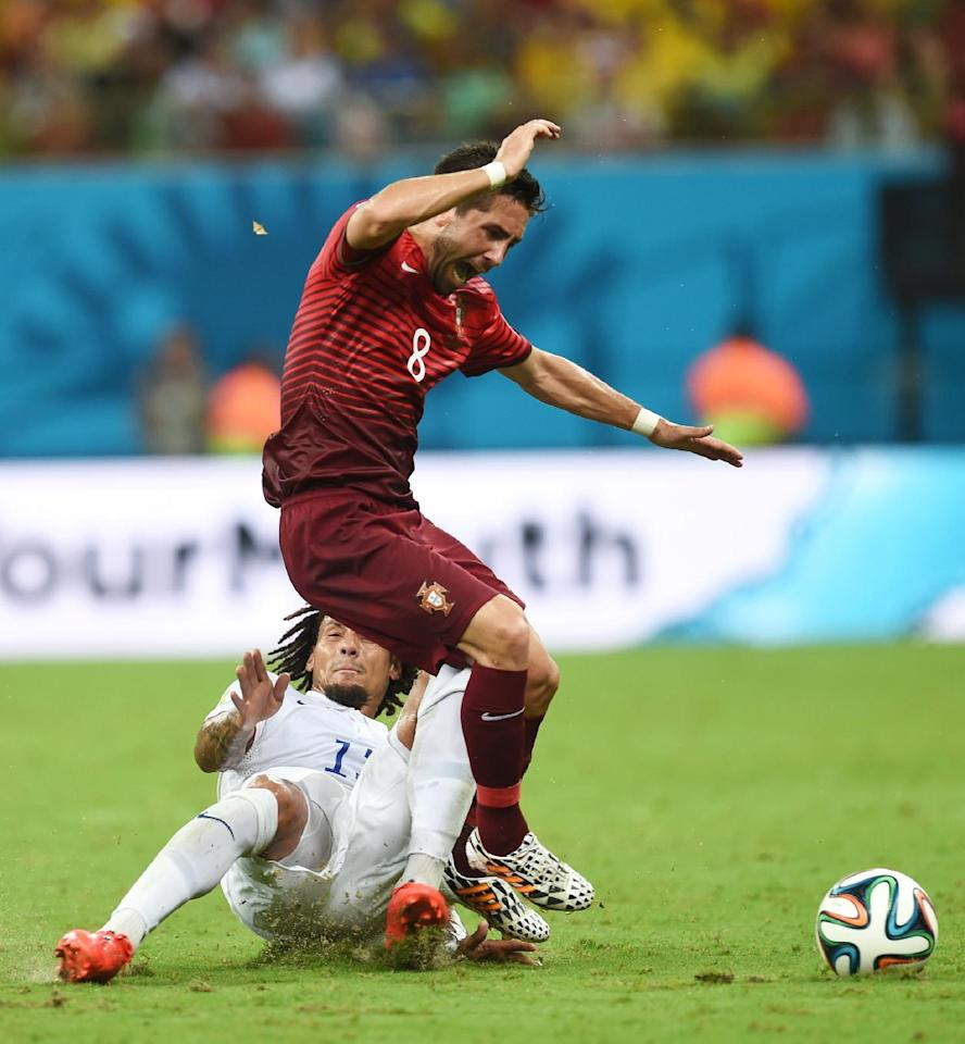 United States' Jermaine Jones, bottom. fouls Portugal's Joao Moutinho during the group G World Cup soccer match between the USA and Portugal at the Arena da Amazonia in Manaus, Brazil, Sunday, June 22, 2014. (AP Photo/Paulo Duarte)