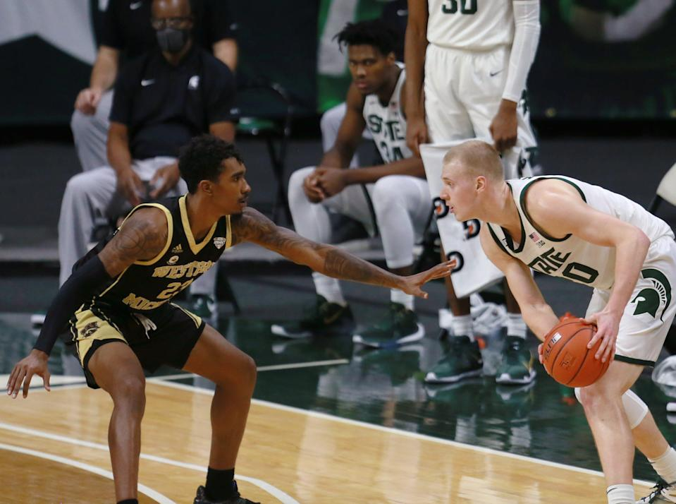 Michigan State's Joey Hauser (20) dribbles against Western Michigan's Greg Lee in the second half on Dec. 6, 2020, in East Lansing.
