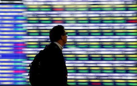 A man walks past an electronic stock quotation board outside a brokerage in Tokyo, Japan, November 13, 2018. REUTERS/Toru Hanai/Files